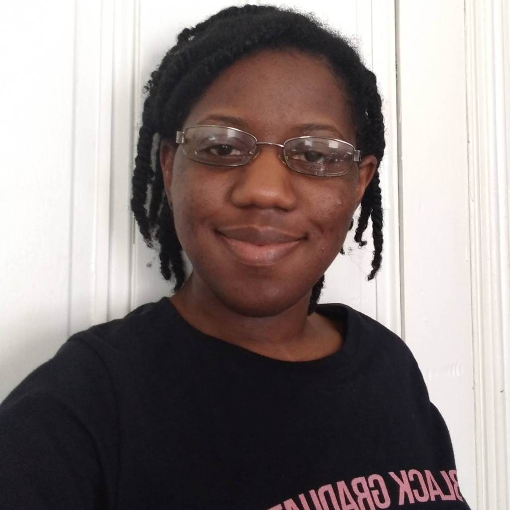 A selfie of Angel standing against a white door and grinning. She is wearing a black shirt with the phrase Black Graduates, though graduates is partially cut off.
