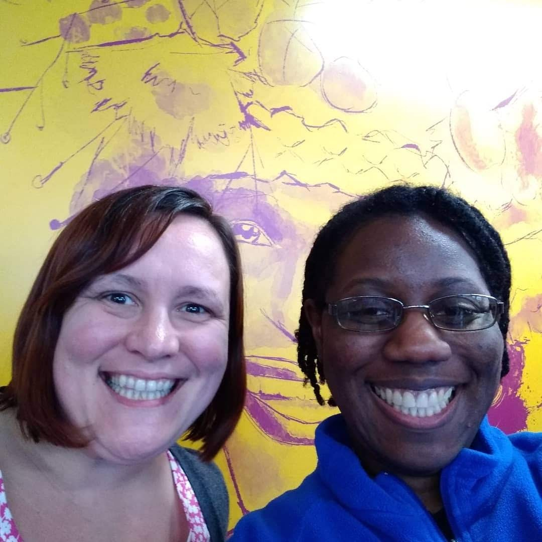 A selfie of a White woman with dark short hair smiling next to Angel, a Black woman with short black hair & glasses smiling. They are standing in front of a yellow wall with Marsha P. Johnson's face drawn on it.